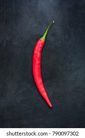Single red chili pepper isolated on dark gray slate