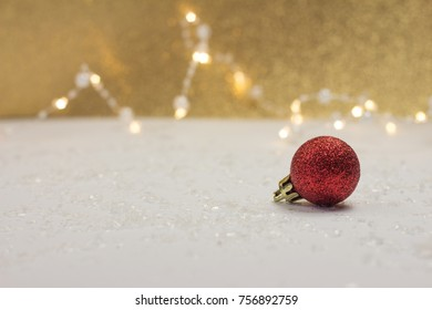 single red christmas ball in front of golden glittering bokeh background
