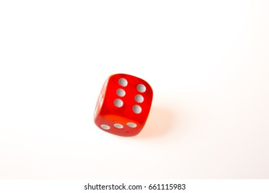 A single red die about to come to a rest with a six showing on the upper face, isolated against a white background
