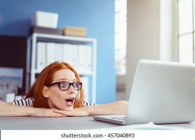 Single red haired young adult female in eyeglasses resting head on hands with surprised expression while looking at something on her laptop computer