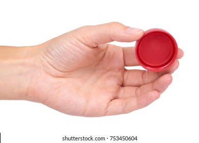 Single red plastic bottle cap in hand isolated on white background