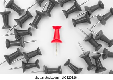 Single red plastic push pin surrounded by scattered gray push pins on white background