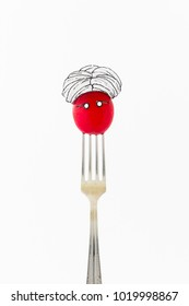 Single red radish on white background with turban sitting as a fakir on top of a silver fork representing indian food.