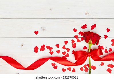 Single red rose on white wooden background with ribbon and confetti hearts