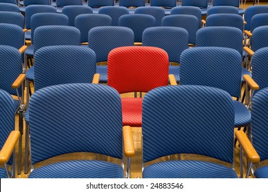 Single red seat in the middle of rows of blue seats
