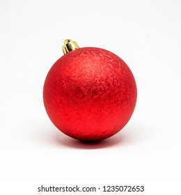 Single red shiny decorative ball with ornaments for a Christmas tree isolated on a white background