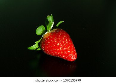 Single red strawberry on black background. Very popular spring and summer fruit.