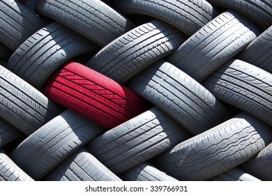 Single red tire in a stack of tires
