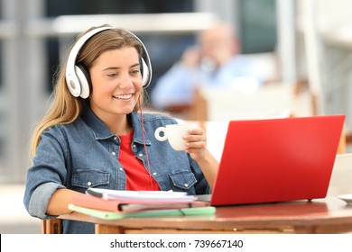 Single relaxed student female watching and listening media content on line sitting in a coffee shop