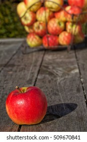 Single ripe apple and other apples in a wire basket in the background on a wooden table outdoors.