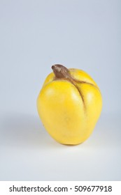 Single ripe quince in front of bright background.