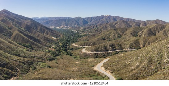 Single road winds into a mountain valley in the hills of southern California's Angeles National Forest.
