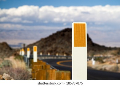 Single roadside safety reflector with others fading in to the distance along a freshly paved canyon road with mountains and clouds in the background.