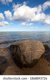 Single rock on the shore, cloudy sky