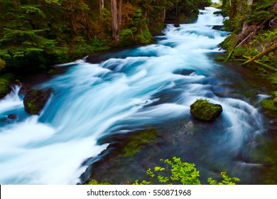 Single rock sits in the midst of a flowing river. Long exposure to smooth out the rapids. Concepts of perseverance, determination, strength and persistence.