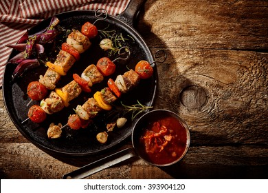 Single round black cast iron frying pan filled with kebabs, garlic, onion and rosemary next to cup of chili sauce over rustic wooden table