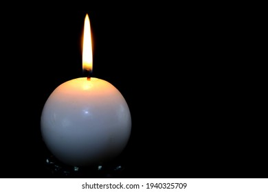 A single round burning candle resting on a glass base with a black background, ready to overlay text or copy on right hand side.