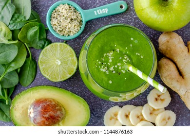 Single round glass filled with green kale and spinach smoothie and green swirled straws surrounded by raw ingredients