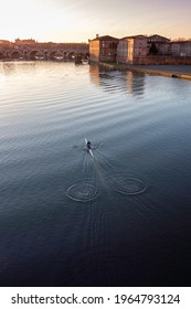 A single rowing competitor, a single rower in the early morning on the river. Soft sunrise lights. Image with  selective focus and toning.