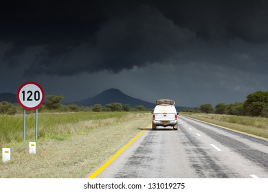 Single safari car traveling in Africa. Namibia. Dark, storm sky.
