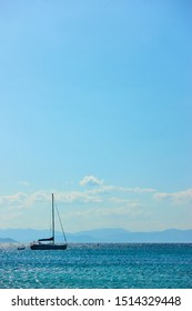 Single sail yacht in the sea near islands and blue sky with clouds. Vertical seascape with large space for your own text