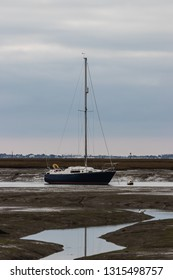 A single sailing boat on the low tide waters with the mast reflecting in the water