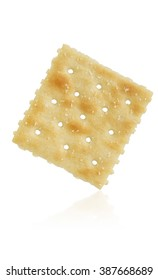 a single saltine cracker on white background with reflection