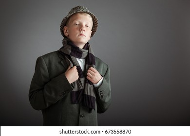 Single serious looking cute blond boy in hat and scarf over gray background with copy space