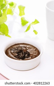 Single Serving of Molten Chocolate Cake baked in white ceramic ramekin, Hot chocolate pudding with fondant centre on plate with tablespoon, cup of tea on the table,  and mint background, close-up