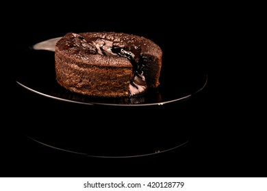 Single Serving of Molten Chocolate Cake on black tales, Hot chocolate pudding with fondant centre on plate isolated on black background , close-up, restaurant image