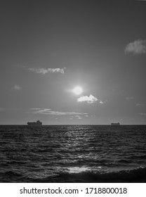 Single ships in the distance at the horizon during sunrise at calm waters of the bay.