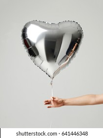 Single silver big heart metallic balloon for birthday isolated on a gray background