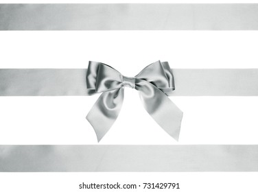 Single silver bow with tails with horizontal satin ribbons for Christmas decorations of boxes on white background