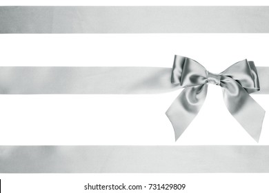 Single silver bow with tails with horizontal satin ribbons for Christmas decorations of boxes isolated on white