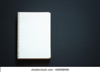 Single simple empty white notebook with a blank for drawing or writing is on a Desktop from black chalkboard. Top view. Mockup. Flat lay