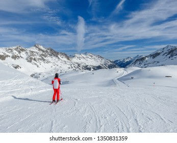 Single skier on empty ski slope in Austrian Alps. Amazing view downhill, perfectly prepared ski slopes, crisp snow. Amazing way to spend spring getaway, relaxing, sporting and enjoying the nature.