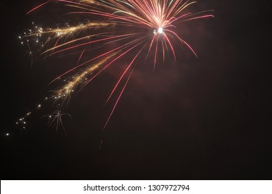 single skyrocket exploding on night sky in red and golden sparkling colors