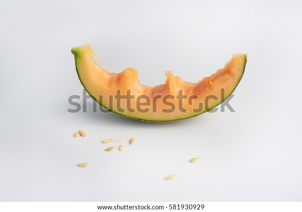 Single slice of a cantaloupe melon with a couple bites taken off it, composition isolated over the white background