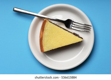 single slice of pie with poppy seeds on white plate near silver fork on bright blue background, top view