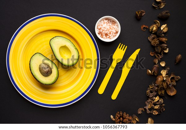Single, sliced avocado on yellow plate. Shot top down. Member of Lauraceae family.