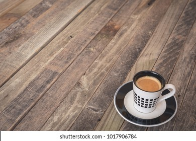 Single small espresso coffee cup on wooden background. Side view.