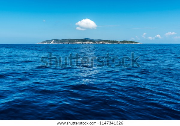 Single Small Island in the blue Ionian Sea with a cloud abouve it