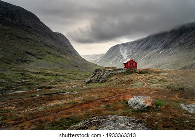 A single small red cabin billows smoke from it's tiny chimney in the remote gorge of central Norway. The distant dark clouds give the feeling of isolation and remoteness. Shot during autumn