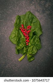 A single spinach leaf with pink pepper on it