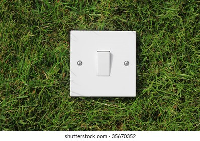 A single square white light switch set on green grass. representing the use of green energy.