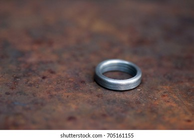 Single steel ring on a rusty surface