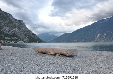 Single stone bench on shore of calm lake and mountains