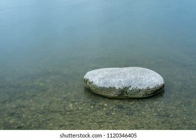 Single stone in water. Long exposure photo during summar day. Blurred surface of water.