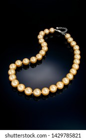 A single strand golden color pearl necklace sits on a black refective background.