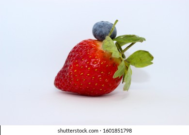 A single strawberry with a single blueberry sat on top on a bright white backround creating food art